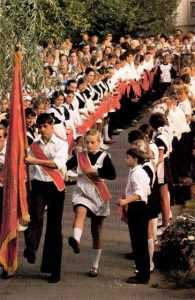 Ceremony of entry into the Pioneer organization, mandatory for children from nine to fourteen. The row on the left: Komsomol members (children fourteen and over) holding the red neck scarfs in preparation to tying them around the new Pioneers' collars. On the right: the just-accepted Pioneers waiting for neck scarfs.