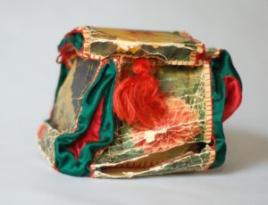 Jewelry box made by Tsipora and Bena as a gift for the International Women's day on March 8, 1958. The box is made from postcards and satin inserts in the corners; the handle is a tassel fashioned from silky threads.