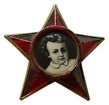 Pin worn by each Oktyabryonok, a member of the Communist Youth organization for children aged 7 to 9. The portrait in the middle is of Lenin as a child. (Photo from https://en.wikipedia.org/wiki/Little_Octobrists).