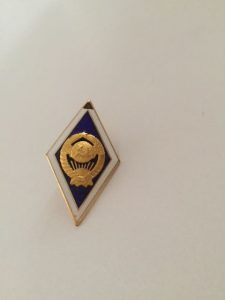 Pin worn by graduates of universities. It is bigger than pins of other schools of higher learning. This pin marks a Masters Degree (Bachelor Degree was not offered). It features the National Emblem of the Soviet Union.