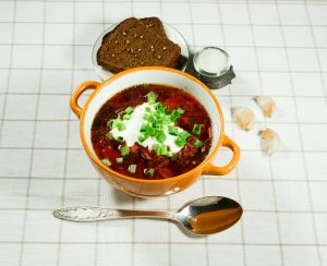 Traditional Ukrainian borscht garnished with green onions and sour cream. Served with rye bread, garlic, and salt. iStock90218121.